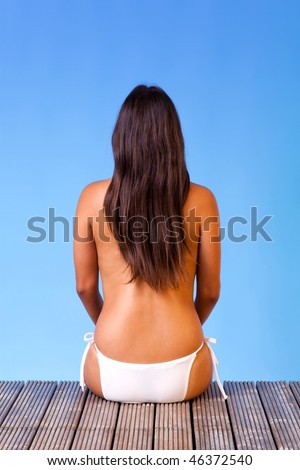 Rear view of a topless young woman wearing white bikini bottoms sat on the end of a wooden pier - stock photo