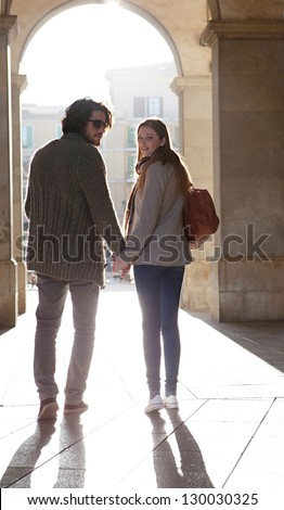 Rear view of a tourist couple silhouette holding hands visiting a destination city, turning while walking under an old arch with the morning sun rays filtering through. - stock photo