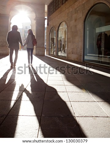 Rear view of a tourist couple silhouette holding hands while visiting a destination city, walking under an old arch with the morning sun rays filtering through. - stock photo
