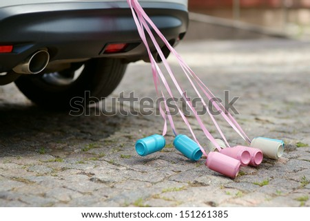 Rear view of a wedding car with cans attached - stock photo