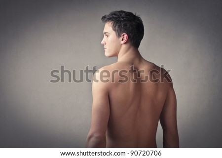 Rear view of a well-built bare-chested young man - stock photo