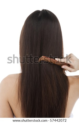 Rear view of a woman combing her hair - stock photo