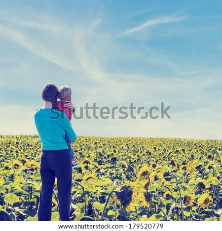 Rear view of a woman holding her child with love and care while looking at a wide sunflower field, under a serene blue sky of summer. Retro filter effect. - stock photo