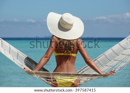 Rear view of a woman in bikini with a stylish hat sitting on a hammock on a beach by the sea - stock photo