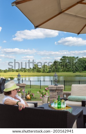 Rear view of a woman relaxing on an outdoor patio enjoying the view over a calm peaceful lake and lush countryside as she enjoys a glass of iced bottled water on a hot summer day - stock photo