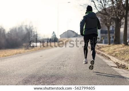 rear view of a woman running in the streets of a little town during winter or autumn, she seems so light that she flies