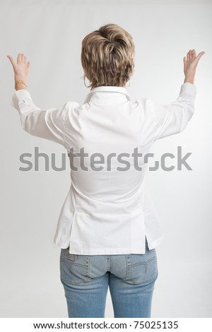 Rear view of a woman showing something with both hands