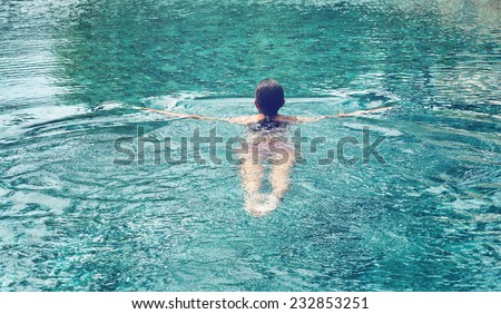 Rear view of a woman swimming at relaxing pool with wide open arms on crystal clear water. - stock photo