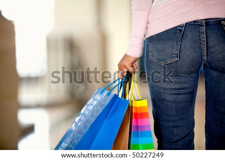 Rear view of a woman with shopping bags in a mall - stock photo