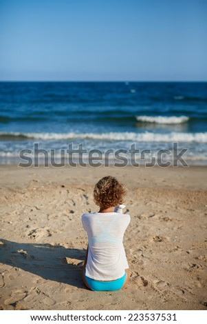Rear view of a young blond  woman wearing in a white shirt and a swimsuit standing on a sea background. Travel and healthy lifestyle.