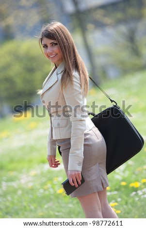 Rear view of a young businesswoman walking outdoors while watching in camera