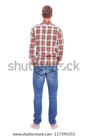 rear view of a young casual man standing with his hands in his pockets - stock photo