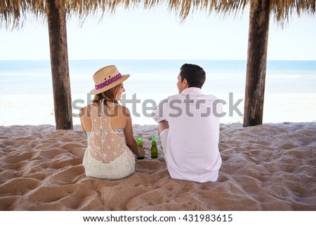 Rear view of a young couple sitting on the sand and drinking some beer during a date at the beach