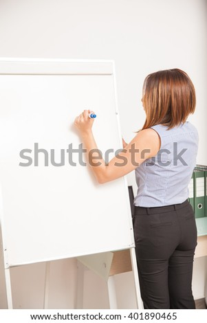 Rear view of a young female teacher writing on a flip chart and giving a class - stock photo