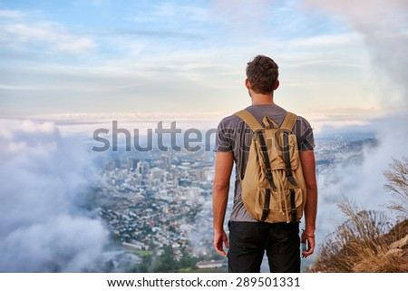 Rear view of a young hiker standing on a mountain path looking out over the city through the clouds - stock photo