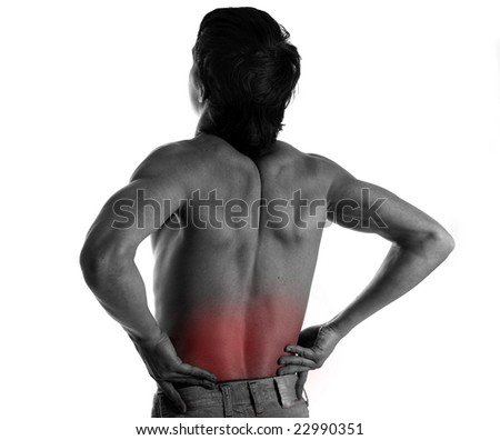 Rear view of a young male. Holding his back in pain. - stock photo