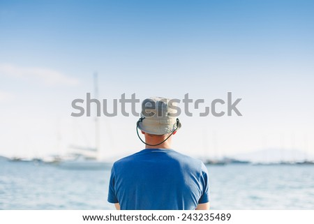 Rear view of a young man and the blue sea during his vacation in an idyllic nature scene destination - stock photo