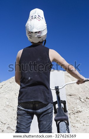 rear view of a young man BMX biker holding his bike on a BMX session in the mountain - focus on the helmet - stock photo