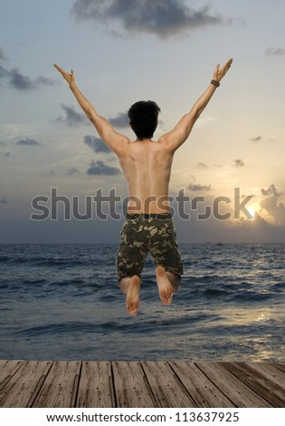 Rear view of a young man jumping with joy over a pier