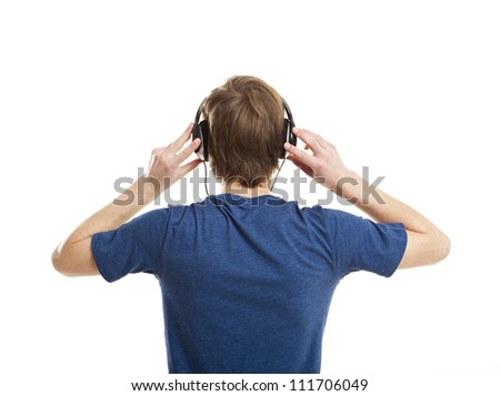Rear view of a young man listening music with headphones, isolated on white background - stock photo