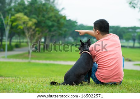 Rear view of a young man sitting on the grass and showing something to his dog  - stock photo