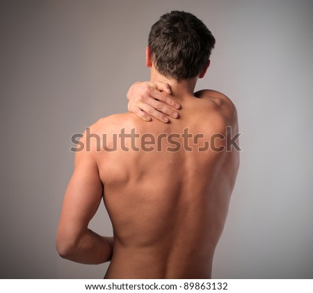 Rear view of a young man suffering from backache - stock photo