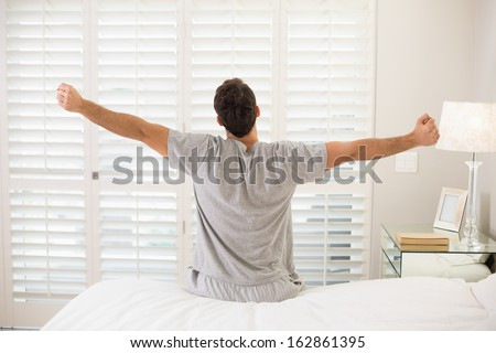 Rear view of a young man waking up in bed and stretching his arms - stock photo