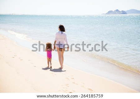 Rear view of a young mother and her daughter holding hands and walking on the beach on a sunny day - stock photo