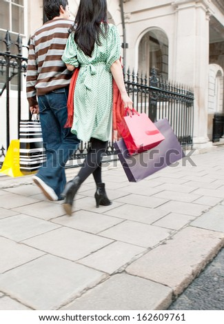 Rear view of a young tourist couple on holiday walking down an exclusive shopping street in the city of London with classic stone buildings together and holding carrier paper bags, outdoors. - stock photo