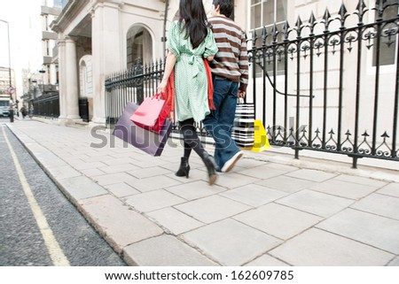 Rear view of a young tourist couple on vacation walking down an exclusive shopping street in the city of London with classic stone buildings together and holding carrier paper bags, outdoors. - stock photo