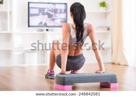 Rear view of a young woman doing home exercises while watching program on television - stock photo