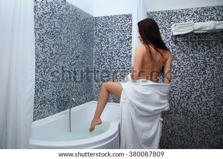 Rear view of a young woman in bathrobe before bathing in the bath. Woman in white bathrobe touching the leg of water  - stock photo