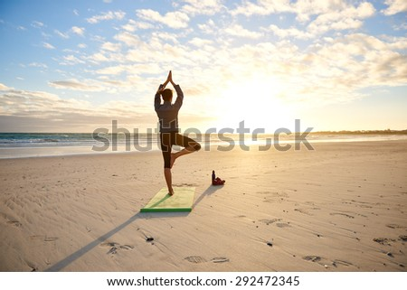 Rear view of a young woman performing the balancing yoga tree pose on a beach early in the morning at sunrise with dramatic clouds and sun flare - stock photo