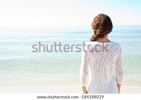 Rear view of a young woman relaxing on a beach, standing and contemplating the clean tranquil sea during a sunny day on vacation. Travel and healthy lifestyle, outdoors. - stock photo