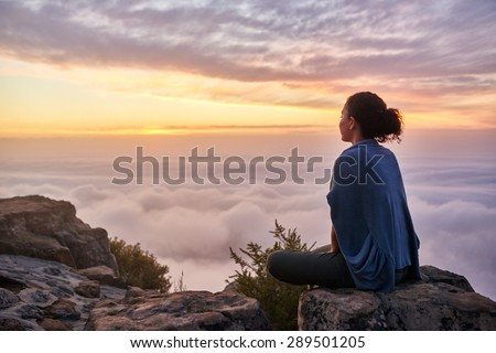 Rear view of a young woman sitting on a mountain top peacefully gazing at low-lying morning clouds and the pastel colours of a tranquil sunrise - stock photo