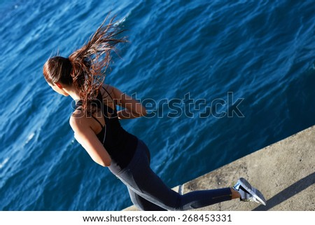 Rear view of a young woman with fitness body running at the seaside next to the ocean, athletic girl jogging over amazing big waves background at sunny day, flying hair in action - stock photo
