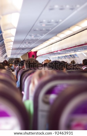 Rear view of aeropane seats with passengers in row - stock photo