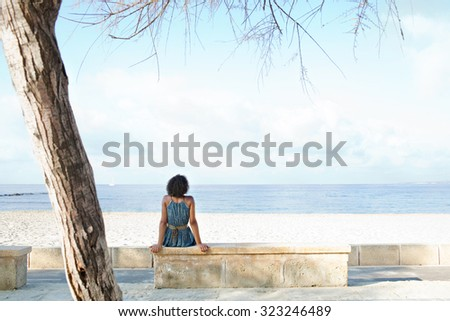 Rear view of african american black young woman sitting on the edge of a white sand beach contemplating the sea on a sunny holiday destination, outdoors. Travel lifestyle and healthy living, exterior. - stock photo