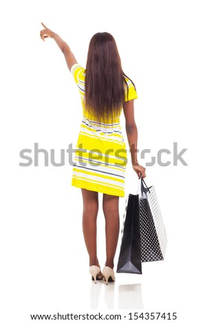 rear view of african american woman pointing with shopping bags isolated on white background - stock photo