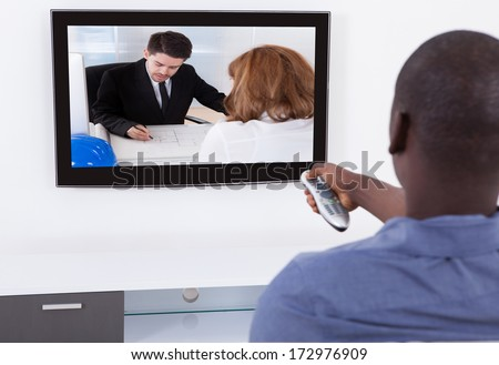 Rear View Of African Man With Remote In Front Of Television - stock photo