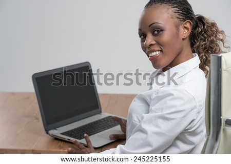 Rear view of african woman working on her laptop - stock photo