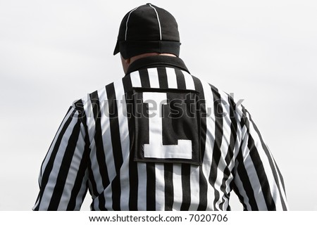 Rear view of American football line judge during a game. - stock photo