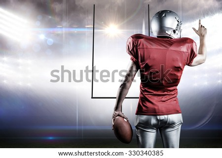 Rear view of American football player pointing while holding ball against american football arena - stock photo