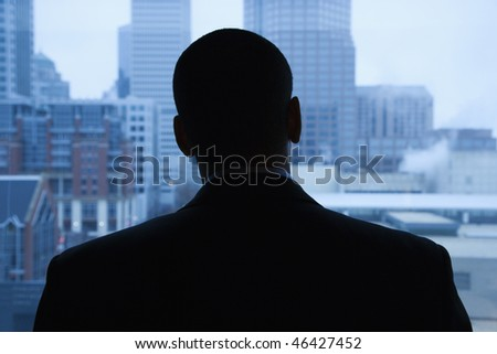 Rear view of an African-American businessman looking out of a window at the city in the distance. Horizontal shot. - stock photo