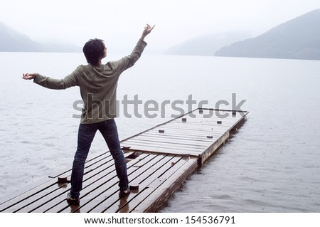 Rear view of an asian japanese man standing on a wooden pier in an impressive lake and mountains landscape doing tai-chi training during a rainy autumn day. - stock photo
