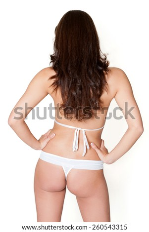 Rear view of an attractive brunette woman in white lingerie in front of white studio  background - stock photo