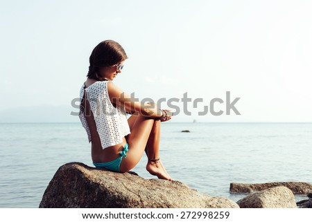 Rear view of an attractive woman sitting and relaxing on a natural coastal rock high up, contemplating the sea against a blue sky. Well being healthy lifestyle
