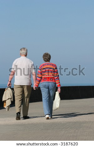 Rear view of an elderly couple walking together and holding hands along a seaside promenade. Set against a blue sky. - stock photo
