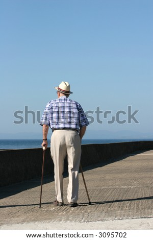 Rear view of an elderly disabled man walking with two walking sticks on a beach promenade. - stock photo