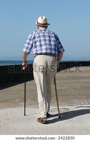 Rear view of an elderly man walking with walking sticks on a beach promenade. - stock photo